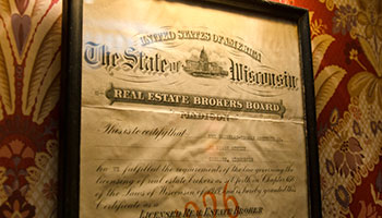 vintage real estate broker bond framed and hanging on a wall